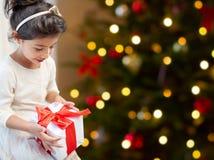 Lycklig liten flicka med julgåvan hemma arkivfoto