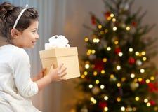 Lycklig liten flicka med julgåvan hemma royaltyfri foto