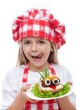 Lycklig liten flicka med kockhatten och den idérika smörgåsen Arkivbilder