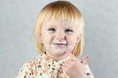 Lycklig liten flicka med kräm på hennes framsida Royaltyfria Bilder
