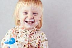 Lycklig liten flicka med kroppkräm Royaltyfri Fotografi