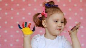 Lycklig liten flicka med målade händer Det roliga barnet med gömma i handflatan i mångfärgad målarfärg stock video