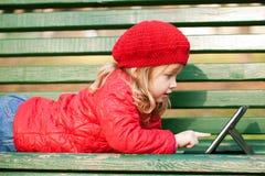 Lycklig liten flicka med minnestavlaPC Royaltyfria Foton