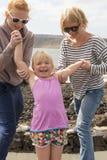 Lycklig liten flicka med modern och storasystern Arkivbilder