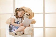 Lycklig liten flicka med nallebjörnen Arkivbild