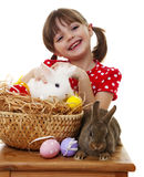 Lycklig liten flicka med två easter kaniner fotografering för bildbyråer