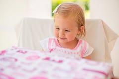 Lycklig liten flicka, når att ha mottagit födelsedaggåva royaltyfria foton