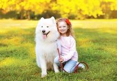 Lycklig liten flicka och hund som har gyckel Royaltyfri Foto