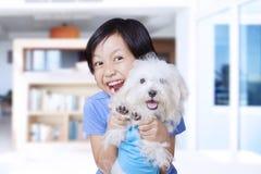 Lycklig liten flicka och maltese hund hemma Royaltyfri Bild