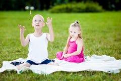 Lycklig liten flicka och pojke i en park royaltyfri bild