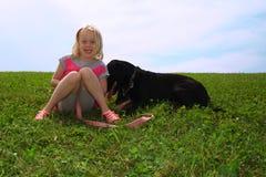 Lycklig liten flicka och svartlabrador arkivbild
