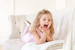 Lycklig liten flicka på den vita soffan arkivfoto