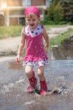 Lycklig liten flicka som bär rosa regnkängor som hoppar in i en pöl Royaltyfri Fotografi