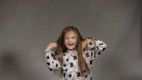 Lycklig liten flicka som fladdrar hår arkivfilmer