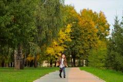 Lycklig liten flicka som går i parkera royaltyfri foto