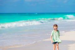 Lycklig liten flicka som går på den vita stranden royaltyfri foto