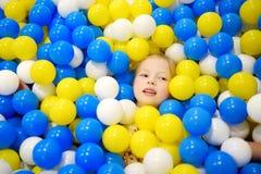 Lycklig liten flicka som har gyckel i bollgrop i lekmitt för ungar inomhus Barn som spelar med färgrika bollar i pöl för lekplats Arkivbild