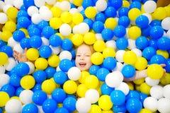 Lycklig liten flicka som har gyckel i bollgrop i lekmitt för ungar inomhus Barn som spelar med färgrika bollar i pöl för lekplats Royaltyfri Foto