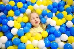 Lycklig liten flicka som har gyckel i bollgrop i lekmitt för ungar inomhus Barn som spelar med färgrika bollar i pöl för lekplats Arkivfoton