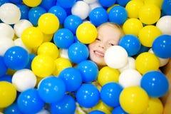 Lycklig liten flicka som har gyckel i bollgrop i lekmitt för ungar inomhus Barn som spelar med färgrika bollar i pöl för lekplats Arkivfoto