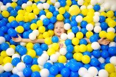 Lycklig liten flicka som har gyckel i bollgrop i lekmitt för ungar inomhus Barn som spelar med färgrika bollar i pöl för lekplats Arkivbilder