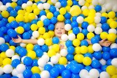 Lycklig liten flicka som har gyckel i bollgrop i lekmitt för ungar inomhus Barn som spelar med färgrika bollar i pöl för lekplats Fotografering för Bildbyråer