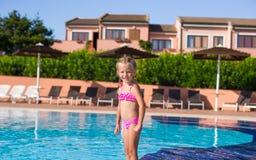 Lycklig liten flicka som har gyckel i simbassängen Fotografering för Bildbyråer
