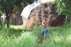 Lycklig liten flicka som kör ner en slingrig bana i bygden Arkivfoton