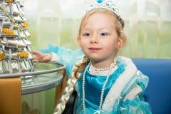 Lycklig liten flicka som kläs som prinsessa i nytt års ferie Arkivfoto