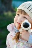 Lycklig liten flicka som kramar hennes favorit- leksak Royaltyfri Bild