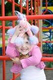 Lycklig liten flicka som kramar hennes favorit- leksak Arkivfoton