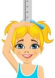Lycklig liten flicka som mäter hennes tillväxt i höjd Fotografering för Bildbyråer