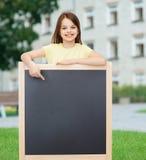 Lycklig liten flicka som pekar fingret till svart tavla Arkivbild