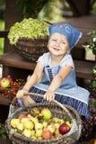 Lycklig liten flicka som rymmer en korg med pears Royaltyfri Foto