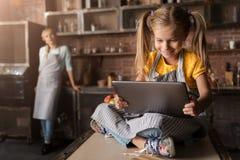 Lycklig liten flicka som ser minnestavlan i köket arkivbild