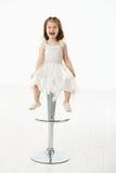 Lycklig liten flicka som sitter på stol Arkivbilder