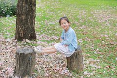 Lycklig liten flicka som sitter på träjournaler mot den fallande rosa blomman i sommarträdgården royaltyfri foto