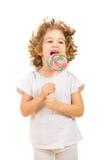 Lycklig liten flicka som slickar en stor klubba Arkivbild