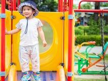 Lycklig liten flicka som spelar glidaren på lekplatsen Barn mummel royaltyfri bild