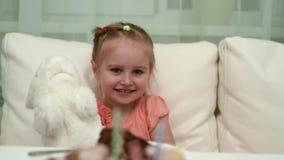 Lycklig liten flicka som spelar hennes leksak på födelsedagtabellen lager videofilmer