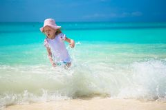 Lycklig liten flicka som spelar i grunt vatten på Arkivfoto