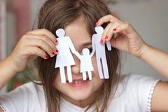 Lycklig liten flicka som spelar med den pappers- chain familjen; lycklig familj Royaltyfria Bilder