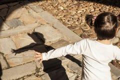 Lycklig liten flicka som spelar med hennes skugga arkivbilder