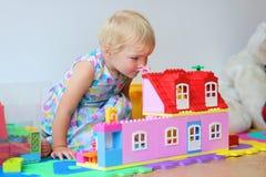 Lycklig liten flicka som spelar med plast- kvarter Royaltyfri Foto
