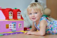Lycklig liten flicka som spelar med plast- kvarter Royaltyfri Fotografi