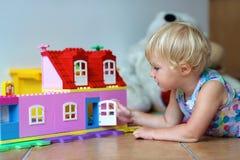 Lycklig liten flicka som spelar med plast- kvarter Royaltyfri Bild