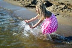 Lycklig liten flicka som spelar med vatten på stranden Royaltyfria Foton