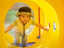 Lycklig liten flicka som spelar på lekplatsen Barn som är lyckliga, fa arkivfoto