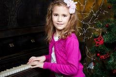 Lycklig liten flicka som spelar pianot royaltyfri foto