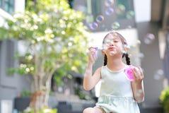 Lycklig liten flicka som spelar såpbubblor i trädgård royaltyfri foto